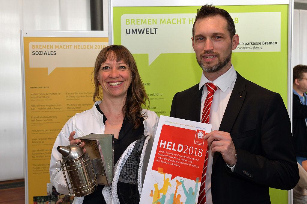 """<span lang=""""DE"""">Anja Kretz, Imkerin der Kinder- und Jugendfarm in Habenhausen (links), und Sparkassen-Kundenberater Jens Gonsior freuen sich über die Förderung für das Bienenprojekt mit Kita-Kindern und Schulklassen. <br /> </span>"""