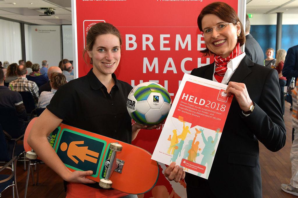 Große Freude mit Fußball und Skatebord: (von links) Laura Alexander, Mitarbeiterin beim Verein Sportgarten e.V., und Dr. Birgit Krull, Direktorin Vorstandsstab und Kommunikation bei der Sparkasse Bremen.