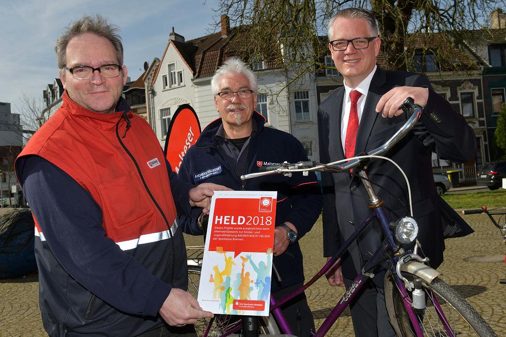 """Björn Ringies (rechts) von der Sparkasse Bremen gratuliert Frank Schönberger und Andreas Kalkosky vom Malteser Hilfswerk zu dem tollen Projekt """"Mobile Fahrradwerkstatt"""" (von links)."""