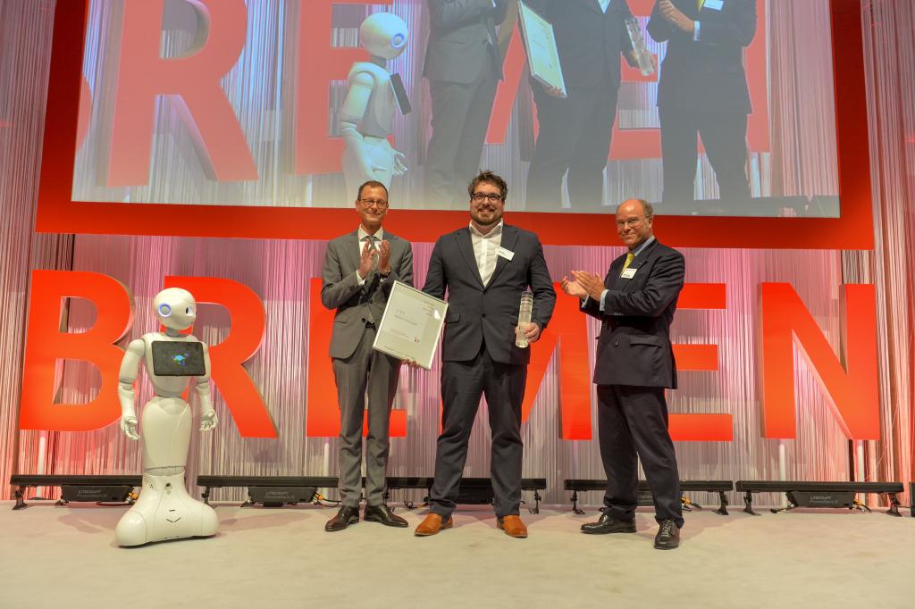 """v.l.n.r. Der Roboter """"Pepper Luna"""", Martin Güntner (Senator für Wirtschaft, Arbeit und Häfen), der Sieger Marc Fiedler (Blackout Technologies) und Dr. Heiko Staroßom (Die Sparkasse Bremen)."""