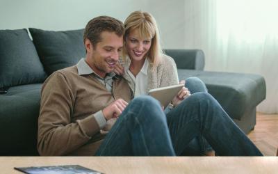 Pärchen arbeitet zuhause digital mit dem Tablet.