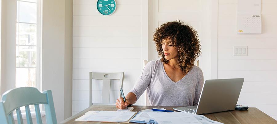 Frau mit Dokumenten und Laptop am Tisch.